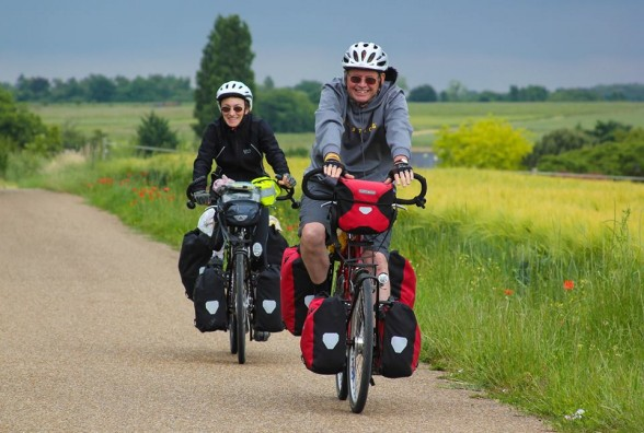 smiling couple on loaded bicycle tour in france