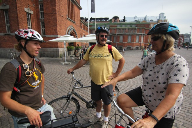 three people on bicycles touring around Helsinki