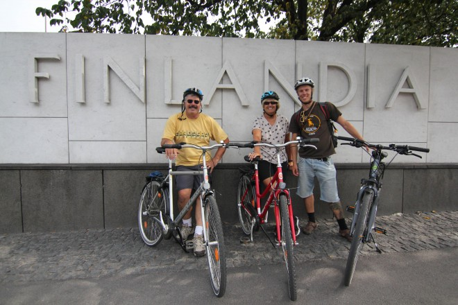 Bike Tours Helsinki - three cyclists in front of FInlandia sign