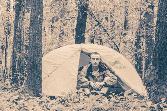 man-camping-in-forest-tent