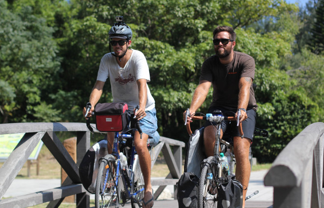 Dylan Brayshaw and Rian Cope riding bicycles over bridge