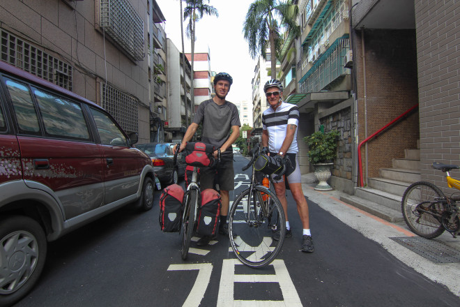 Darren Alff and Kevin Burrett posing with their bicycles at the start of their bicycle tour around the island of Taiwan