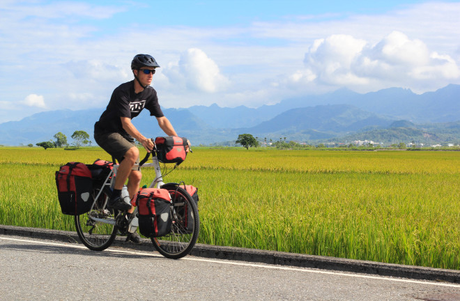 fully-loaded bicycle tourist man on road in taiwan's rift valley