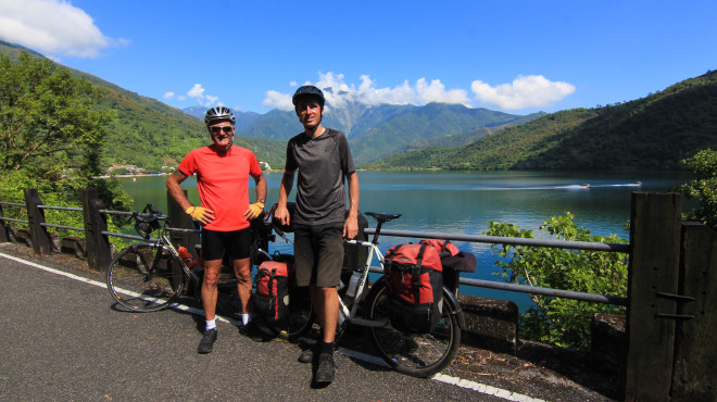 Bicycle TOuring Pro Darren Alff and friend Kevin Burrett smile for a photo with their loaded bicycles at Taiwan's second largest lake