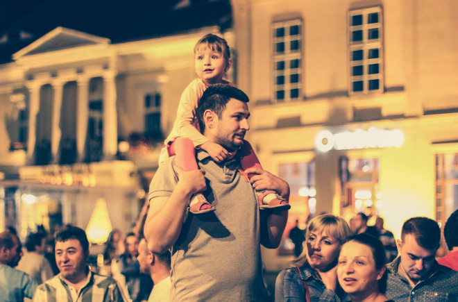 little girl riding on burly mans shoulders