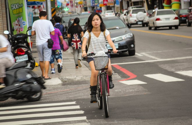 young taiwanese girl riding a bicycle across the street