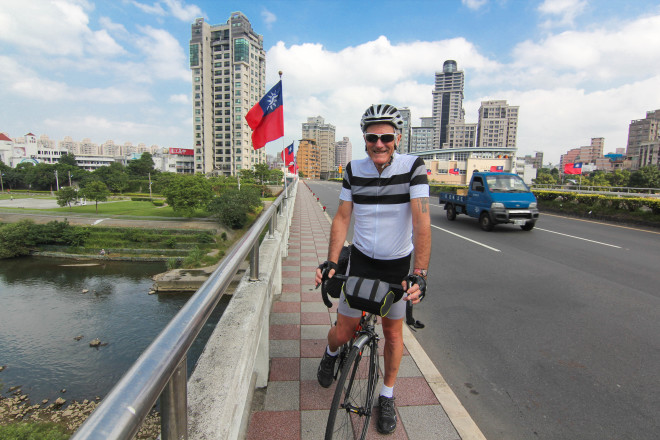 Kevin Burrett cycles with taiwan flags in background of Taipei
