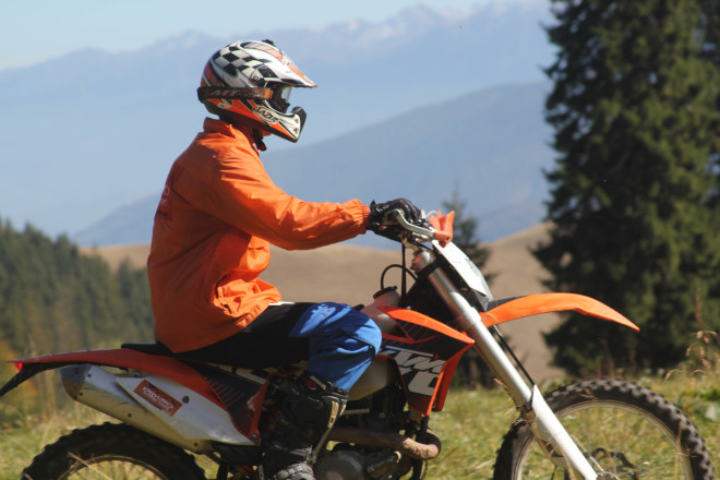 man in orange jacket riding a ktm motorcycle off road in romanian mountains