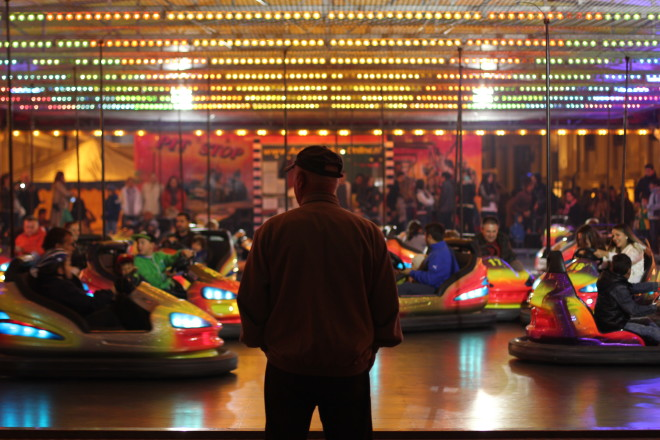 old man watching younger people driving bumper cars