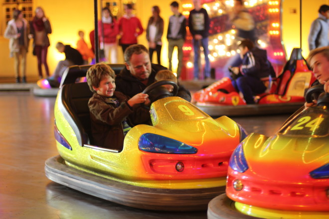 father and son struggling to drive bumper car together