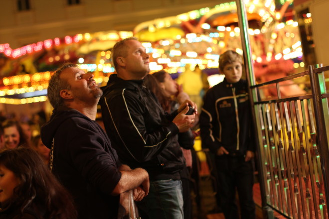 two grown men with young son looking at festival lights and ride