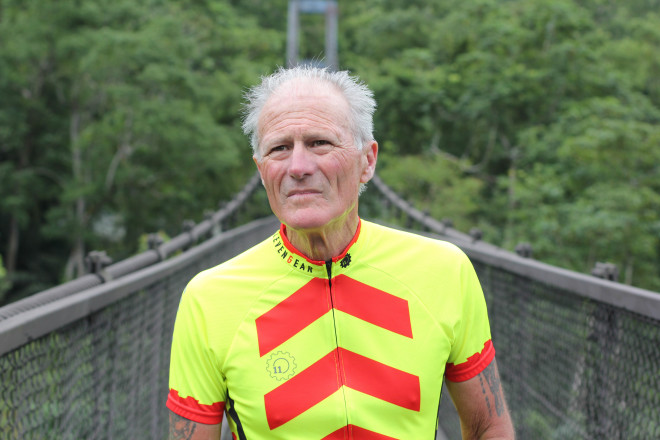 white haired man in bright neon yellow and red cycling jersey