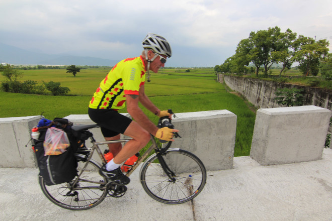neon yellow cyclist riding uphill past rice fields