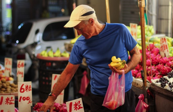 tourist buying fruit from street stall