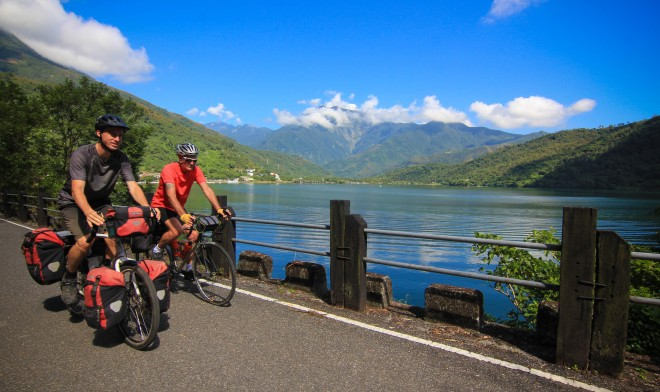 two bicycle tourists riding past liyu lake in taiwan