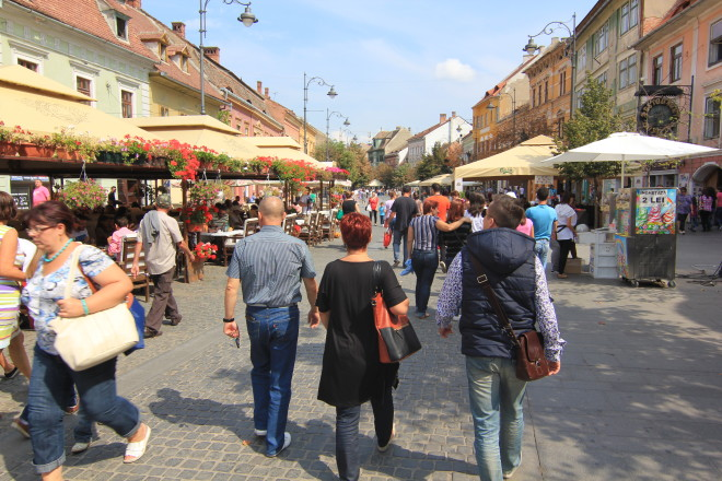tourists walking the main pedestrian street in sibiu romania
