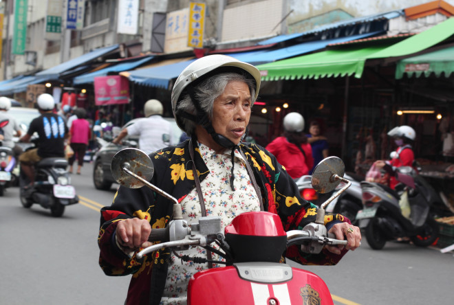 old taiwan woman riding a bright red motor scooter