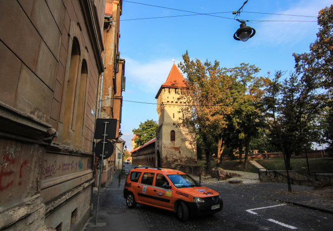 orange taxi cab and sibiu romania city wall towers
