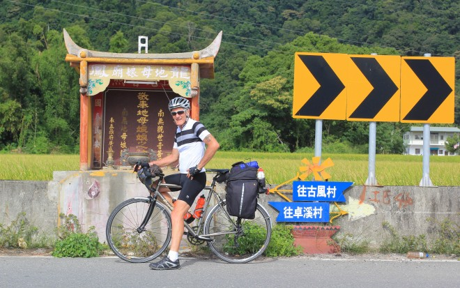 cyclist stopped at roadside church alter in taiwan