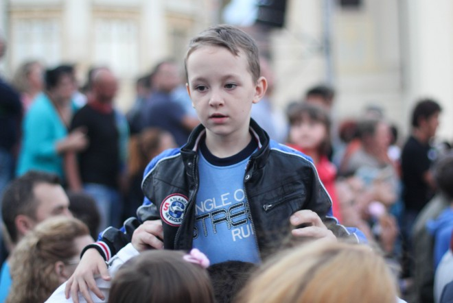 boy in blue shirt above a crowd of people