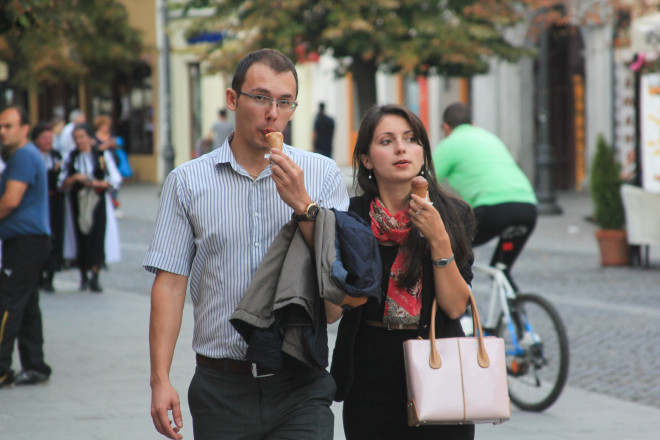 man and woman walking down street and eating ice cream cones