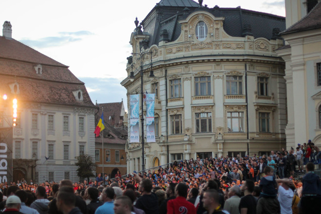 crowd of peopel watching event in sibiu romania central square and city hall in the background