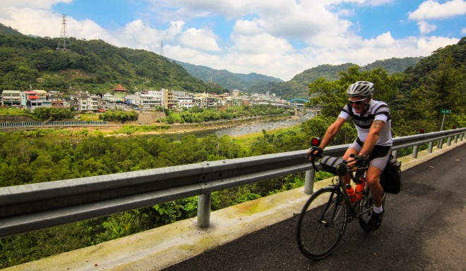 man cycles past taiwan city
