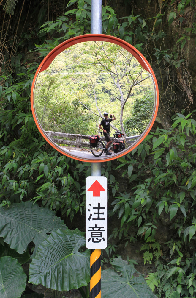 cyclist taking photo using road mirror