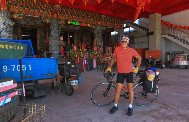 cyclist takes a rest in the shade a tao temple