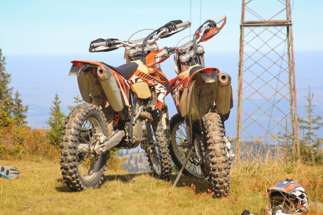 two orange ktm motorcycles leaning up against one another