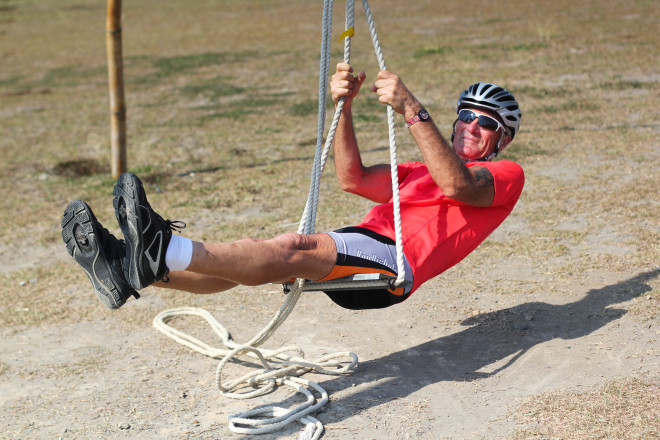 man in orange shirt swings from bamboo swing