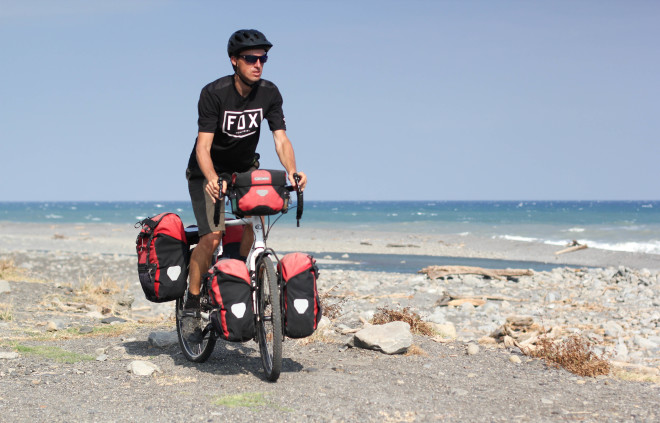 Man in black clothing riding a bicycle along the beach in Asia