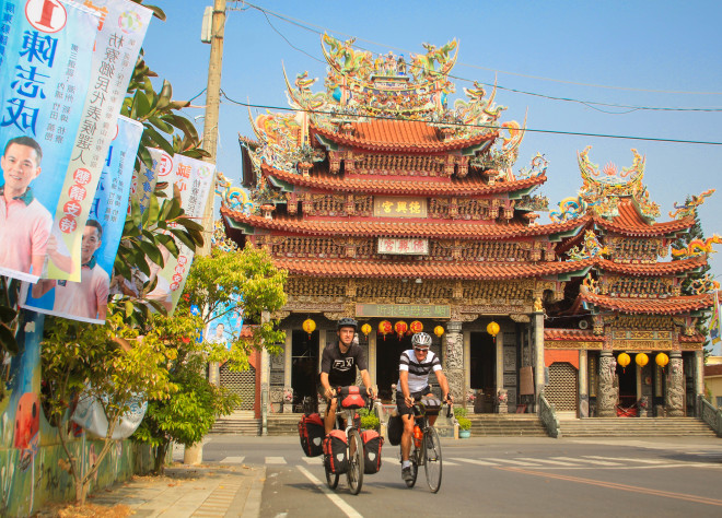 Two bicycle tourists riding past an impressive Tao Temple in Taiwan
