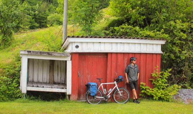 resting a loaded touring bike up against a red barn